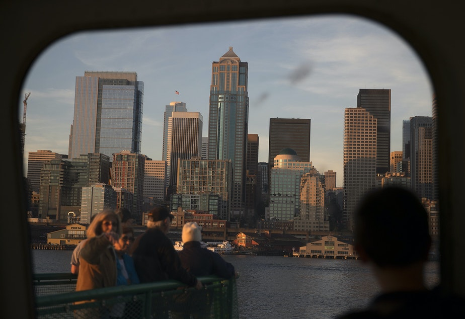 caption: Ferry riders look toward downtown Seattle shortly before arriving from Bremerton on a ferry on Thursday, June 29, 2017, in Seattle.