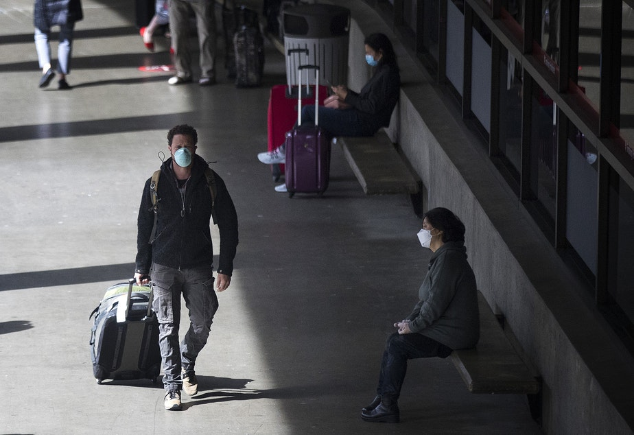 caption: Masked travelers exit Seattle-Tacoma International Airport on Monday, May 18, 2020, in Seattle. All passengers and employees traveling through the airport are required to wear face coverings beginning today, Monday, May 18.