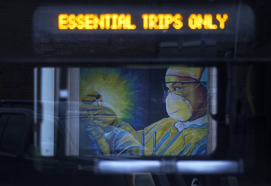caption: A mural of a health care worker painted by artist Jay Mason is shown through the window of a passing King County Metro bus on Tuesday, April 28, 2020, along South Main Street in Seattle.
