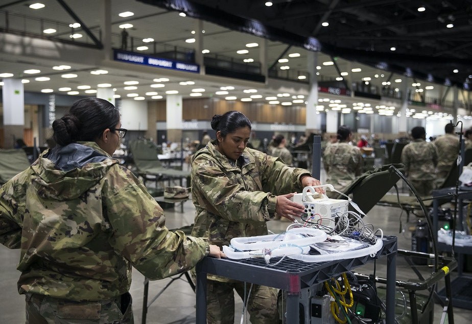 caption: U.S. Army soldiers Viviana Alvarez, left, and Maria Cuevas, right, from the 627th Army Hospital from Fort Carson, Colorado, set up patient monitors in the ICU area of a 250-bed military field hospital being deployed alongside soldiers from Joint Base Lewis-McChord on Tuesday, March 31, 2020, at the CenturyLink Field Event Center in Seattle. The hospital will be for non COVID-19 patients.