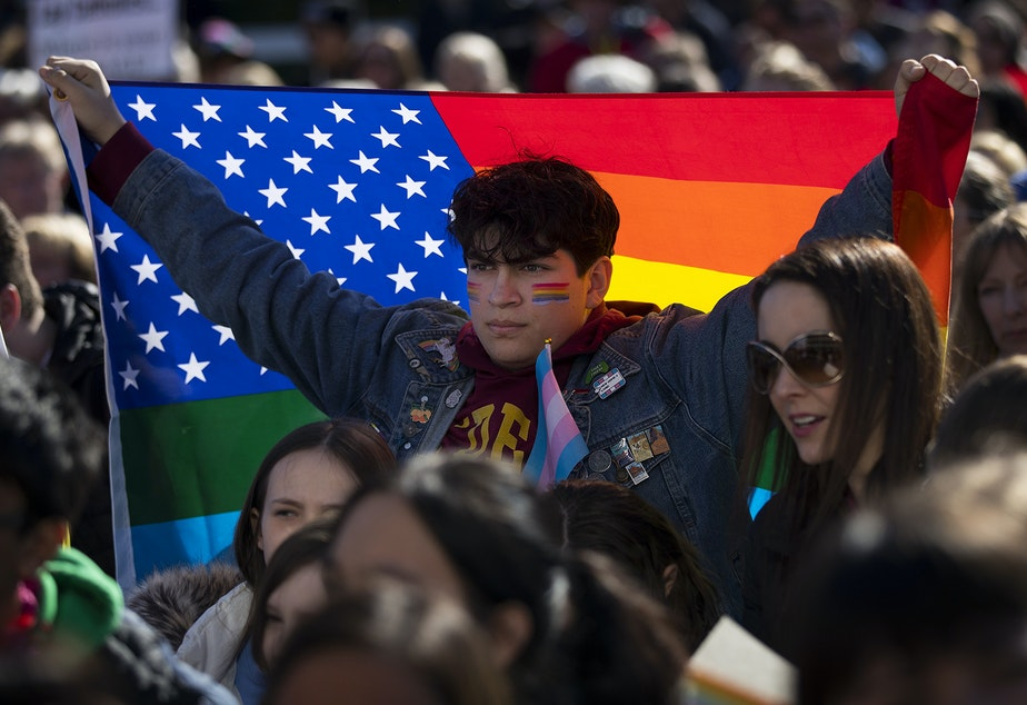 "caption: Nicolas Velasquez, 17, holds a rainbow flag during a walkout to protest the departure of two LGBT educators on Tuesday, February 18, 2020, at Kennedy Catholic High School in Burien. ""I don't think that it's okay that this is happening now,"" Velasquez said. ""I want to be the change that I want to see."""