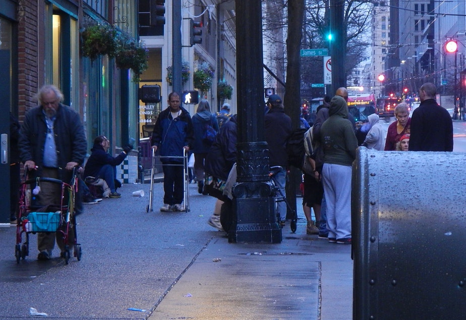 caption: Crowds of homeless people often gather on the sidewalks of downtown Seattle near social-service providers.