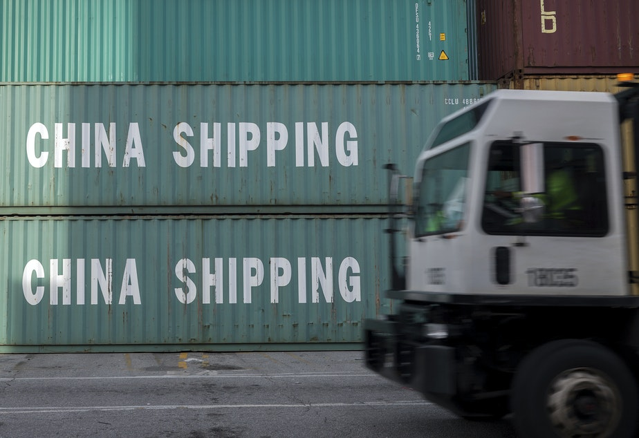caption: A truck passes a stack of China Shipping containers at the Port of Savannah in Georgia on July 5, 2018. The Trump administration is delaying some tariffs from taking effect until December.
