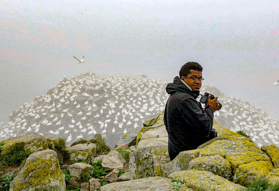 """caption: Jason Ward looking at Northern Gannets in Newfoundland, Canada. Ward is the host of """"Birds of North America,"""" a documentary series on YouTube. He says about a dozen birding Facebook groups around the country have been actively squelching conversations about race."""