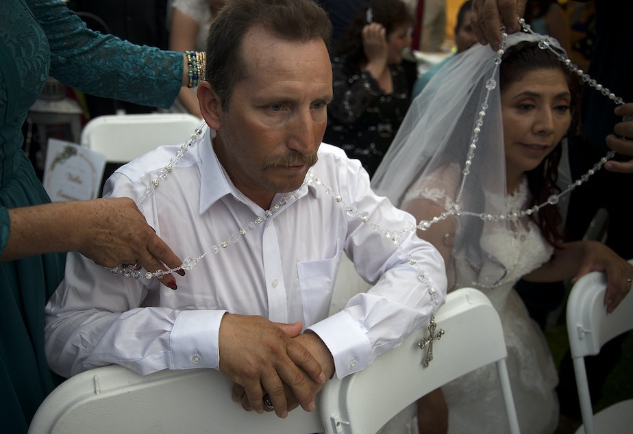 caption: A lasso de boda is placed around newlyweds Isidro Gómez and his wife Genoveva on Sunday, June 2, 2019, during a mass wedding ceremony where 23 couples were married at Our Lady of the Desert Church in Mattawa.