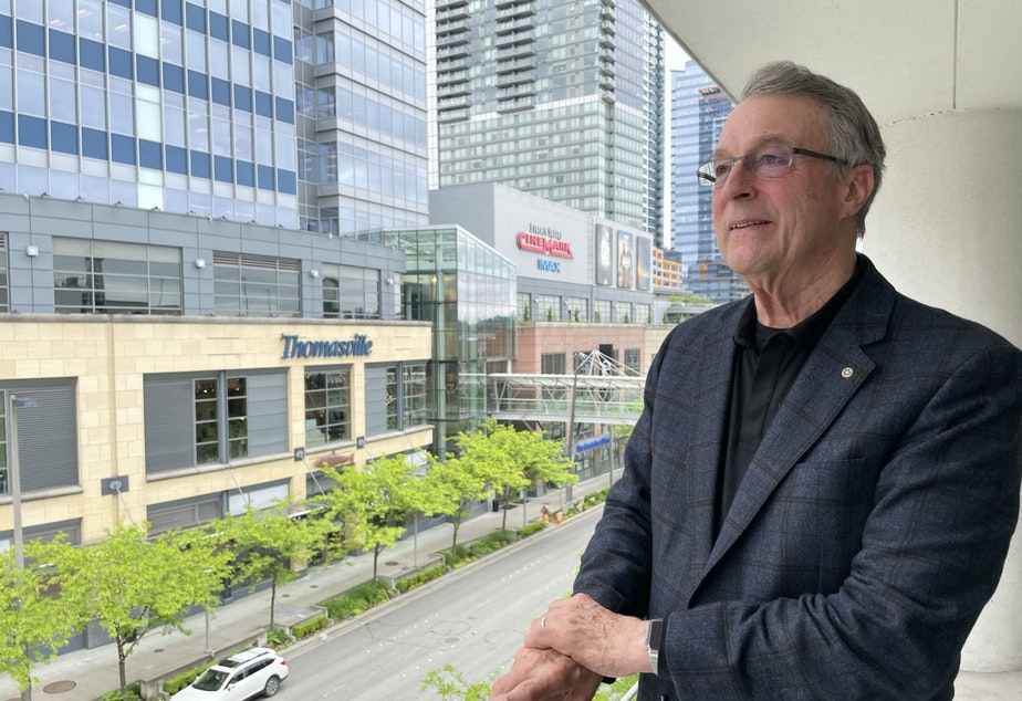 caption: Kemper Freeman on a balcony overlooking Bellevue Way.