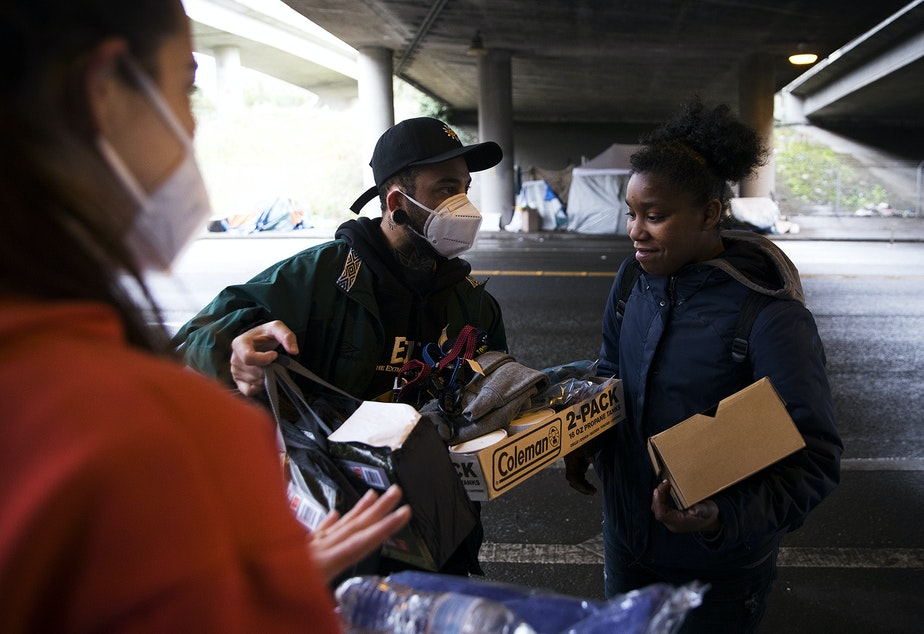 caption: From left, Joscelyn and Cass DuVani deliver a new tent, shoes, clothing, soup, and a tarp, along with several other items to Tedra, 24, who is currently experiencing houselessness, on Friday, March 5, 2021, underneath Interstate 5 along South Dearborn Street in Seattle. Tedra's tent and belongings had been damaged after catching fire the previous evening. KUOW Photo/Megan Farmer