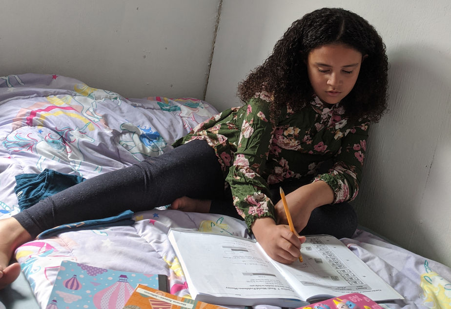 caption: Eight-year-old Mariana Aceves does her homework on her bed inside a tiny home.