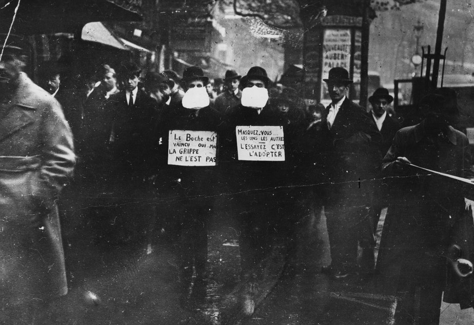 caption: Two men wearing and advocating the use of flu masks in Paris during the Spanish flu epidemic which followed World War I.  (Topical Press Agency/Getty Images)