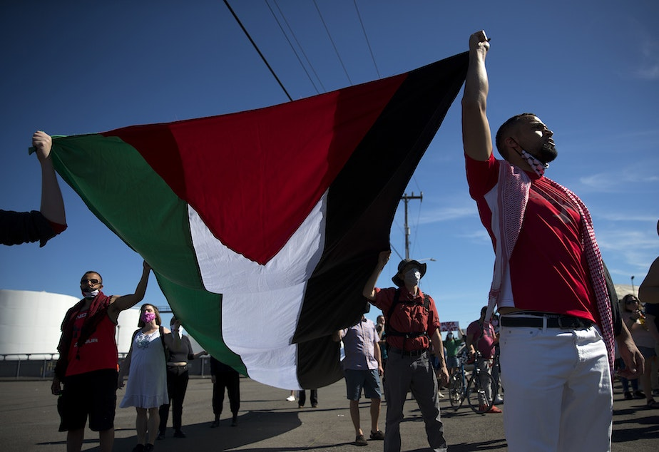 """caption: Activists and allies of the Palestinian feminist organization Falastiniyat, including Omar Elseaidy, right, carry the flag of Palestine while blocking an intersection in protest of the ZIM San Diego vessel, on Thursday, June 17, 2021, at the Port of Seattle. """"We are now calling on our city officials to stand behind their communities against Israeli human rights abuses, and not to give into the bullying of the apartheid state of Israel,"""" said Aisha Mansour, a representative of Falastiniyat."""
