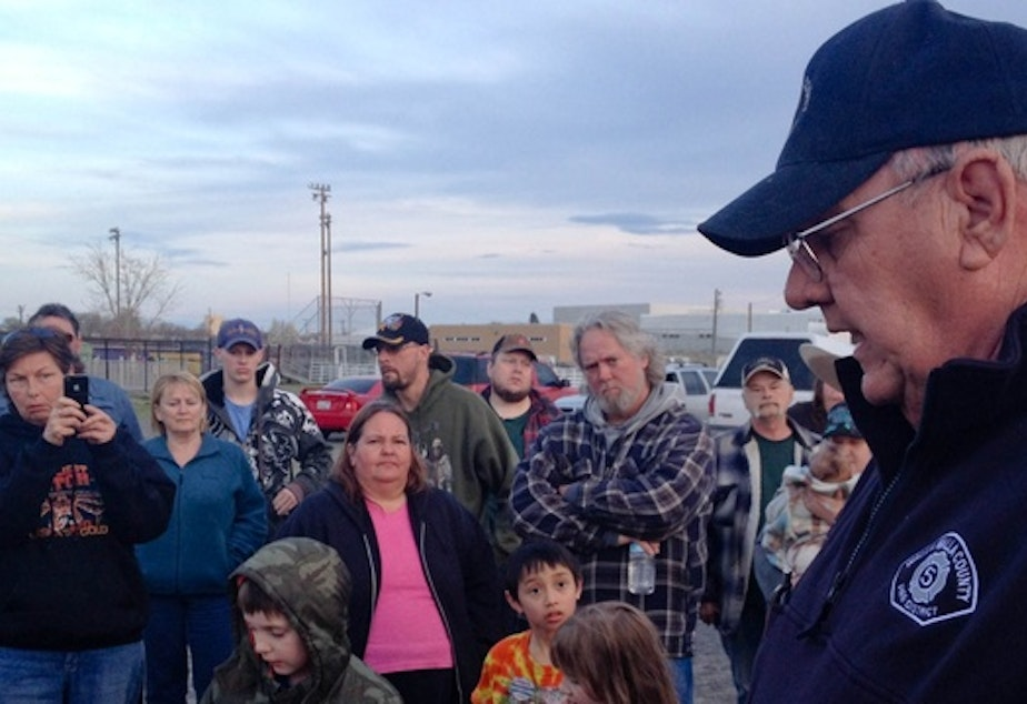 caption:  Duane VanBeek tells Plymouth residents that the evacuation zone had been reduced to one mile. An explosion at an LNG storage tank forced them from their homes Monday morning. Many returned home after spending the day at the Umatilla County Fairgrounds.