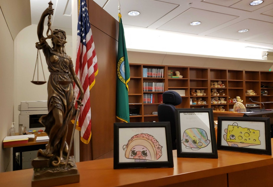 caption: Inside Judge Rajul's court room, Lady Justice stands next to framed coloring pages she's received from migrant children. In the background, rows of teddy bears wait to support youth during the long immigration process.