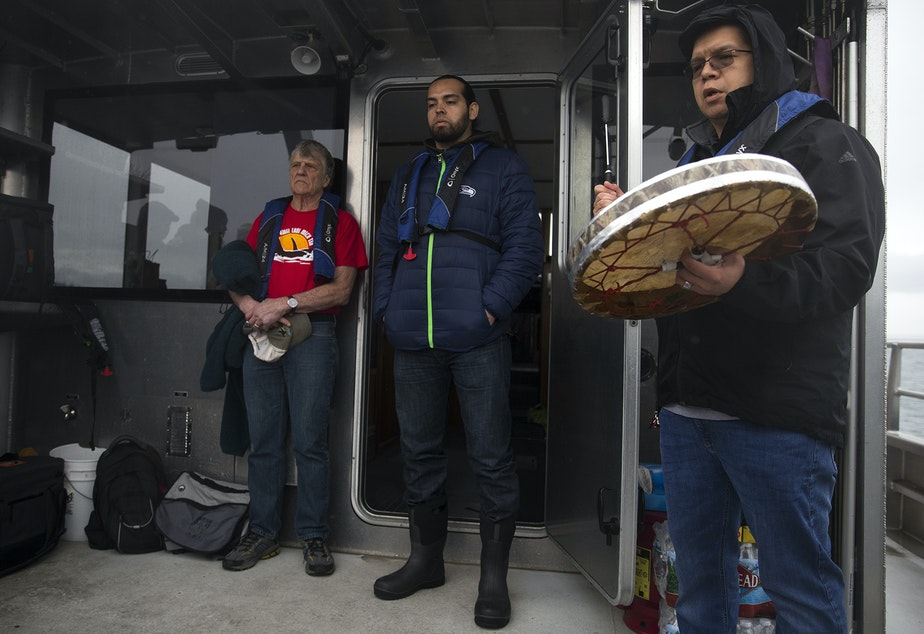 From left, Kurt Russo and Tony Hillaire listen as Lawrence Solomon, right, sings the Lummi National Anthem before a ceremonial feeding where one live chinook salmon was released into the water, aboard King County Research Vessel SoundGuardian on Wednesday, April 10, 2019, near Henry Island.