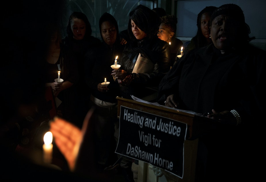 caption: LaDonna Horne, center, holds a candle during a healing and justice vigil for her son, DaShawn Horne, on Saturday, February 3, 2018, outside of the hospital at Harborview Park in Seattle.