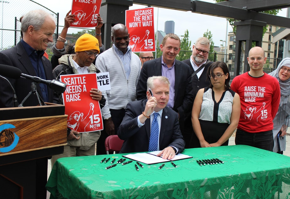 caption: A day after it received final approval in City Council, Seattle Mayor Ed Murray signs the new $15 an hour minimum wage law