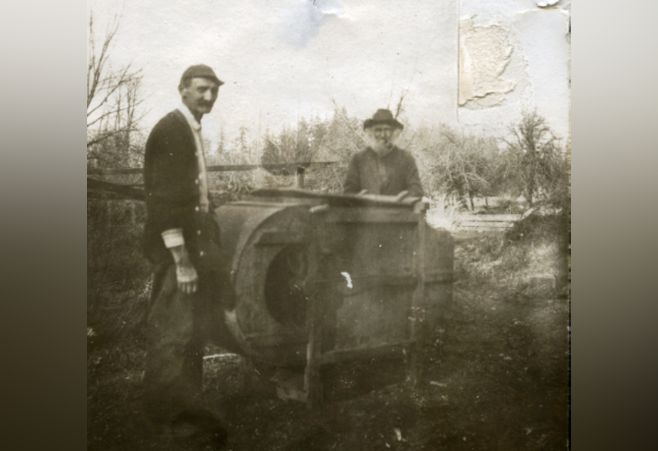 caption: Black pioneer George Bush's grandson, left, and son, right, stand next to a fanning mill on the family's farm near present day Tumwater, Washington. A monument to George Bush and his family is planned for Washington's Capitol Campus.