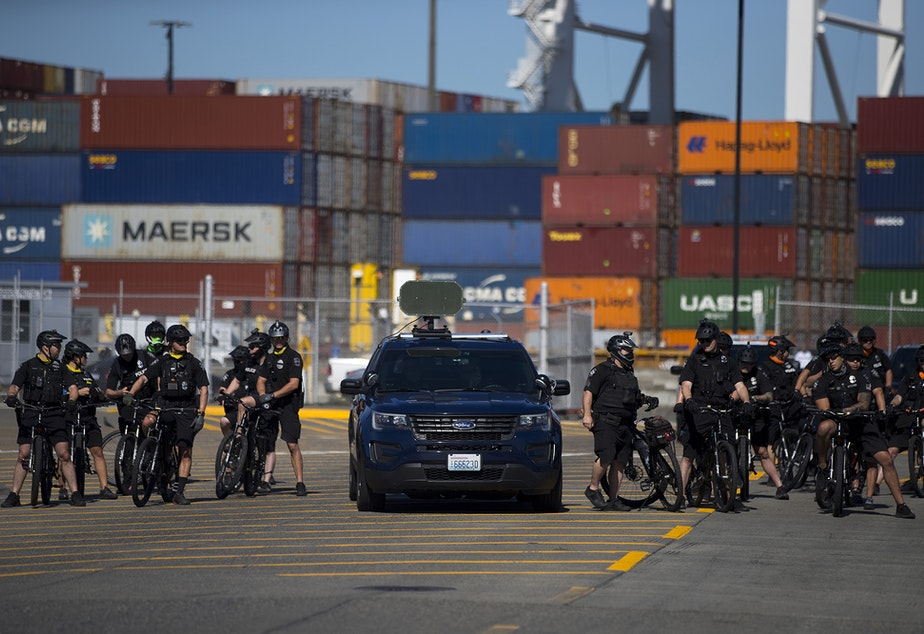 caption: Seattle police officers are shown shortly before giving dispersal orders to activists and allies of the Palestinian feminist organization Falastiniyat, who blocked an intersection in protest of the Israeli Zim San Diego Vessel, on Thursday, June 17, 2021, at the Port of Seattle.