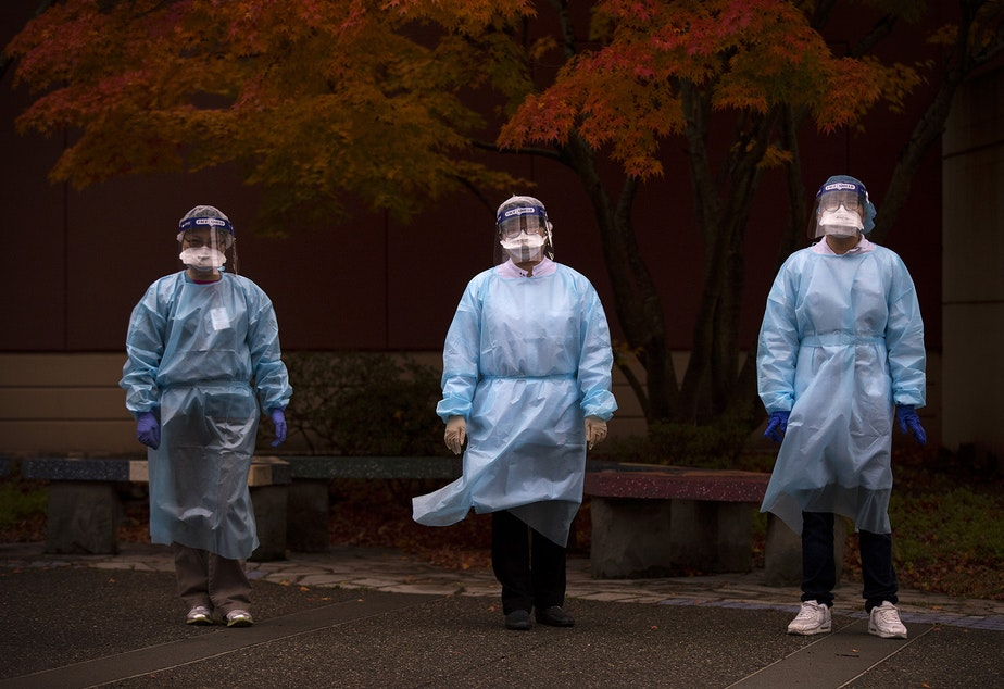 caption: From left, registered nurse Shu Kuang, registered nurse Tina Nguyen and patient services representative Denny Ho stand for a portrait following a shift of Covid-19 testing on Friday, November 20, 2020, at the International Community Health Services drive thru testing site on 8th Avenue South in Seattle's International District.