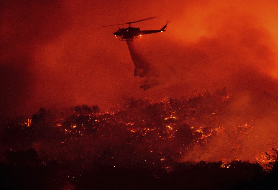 caption: A helicopter drops water on the Cave Fire burning in the Los Padres National Forest above Santa Barbara, Calif., on Tuesday.