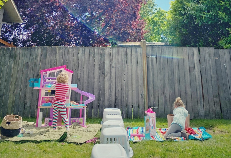 caption: Beatrice, 4, spends time outdoors playing with a new friend she met during the pandemic, on Tuesday, May 19, in Seattle. Their parents set up laundry baskets as a barrier to keep them physically distanced.