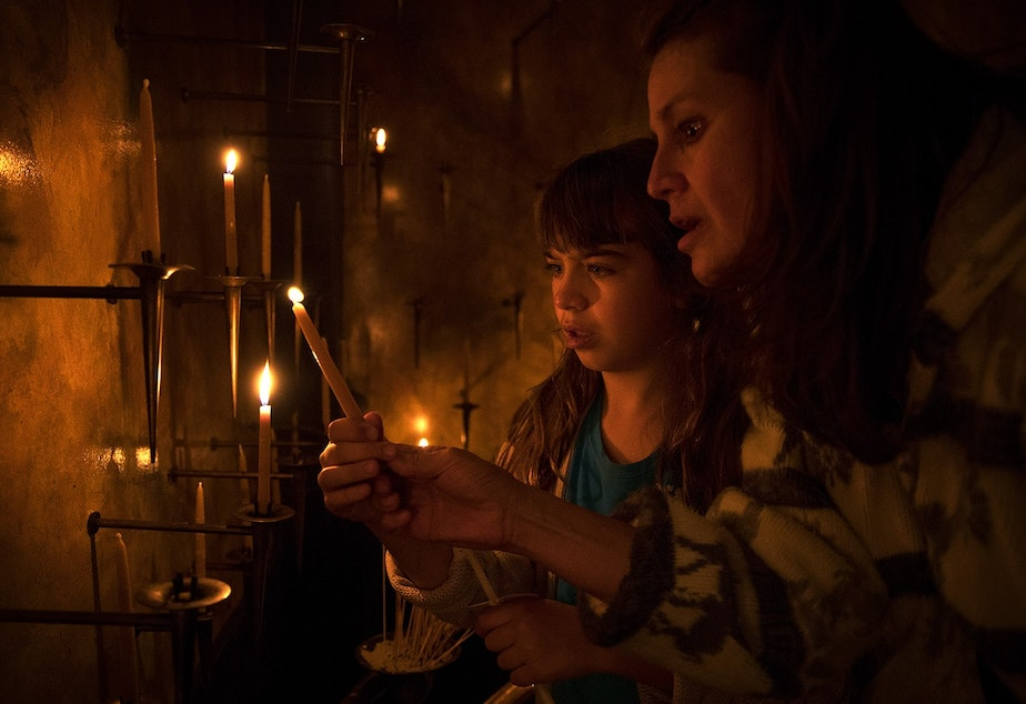 Mariela Mahoney-Armas, 9, left, and Anni Armas light candles on Thursday, June 21, 2018, during a prayer and procession for families at the border at St. James Cathedral in Seattle.
