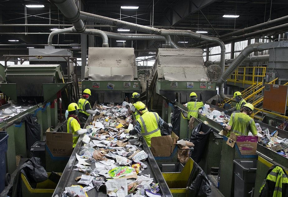caption: Employees remove items that cannot be recycled from a conveyer belt on Friday, October 26, 2018, at Cascade Recycling Center in Woodinville.