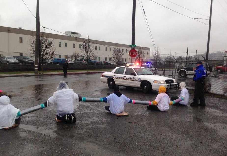 """caption: A dozen protesters block the entrance to the Northwest Detention Center in Tacoma in February 2014. """"I'm shocked to hear ... the kinds of abuse, sexual and otherwise that seems to be occurring,"""" said Martin Castro of the federal civil rights commission."""