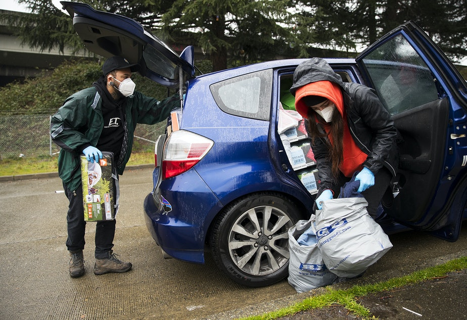 caption: Cass and Joscelyn DuVani deliver tents, sleeping bags, shoes, hot soup, cookies, portable power packs, tarps,  clothing, and several other items to unhoused community members on Friday, March 5, 2021, near the intersection of 10th Avenue South and South Dearborn Street in Seattle.