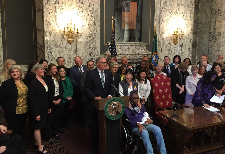 caption: Washington Gov. Jay Inslee signed two historic bills into law on Monday. One creates a public health insurance option, the other a new long-term care benefit.