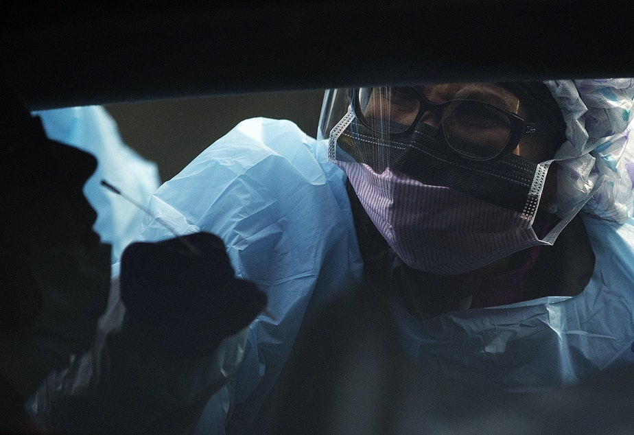 caption: A UW Medicine patient is tested for coronavirus by a UW Medicine nurse on Tuesday, March 17, 2020, at the University of Washington Northwest Outpatient Medical Center on Meridian Avenue North in Seattle.