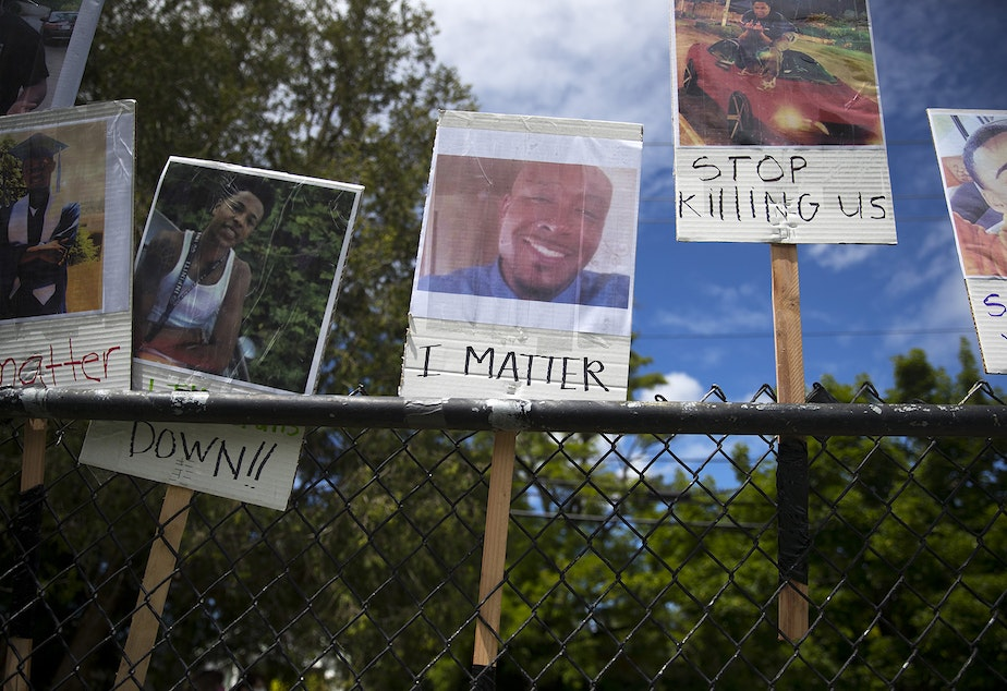 caption: FILE: A photograph of Manuel Ellis, center, is displayed on a fence along with other Black Americans who were unjustly killed by police officers ahead of the We Want to Live march for Black lives on Sunday June 7, 2020, at Othello Park in Seattle. Ellis was killed by Tacoma police officers on March 3rd.
