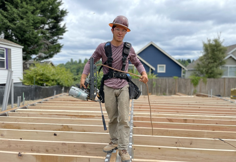 caption: Elio Gonzalez finishes off the first floor at a Madison Valley building site in Seattle.