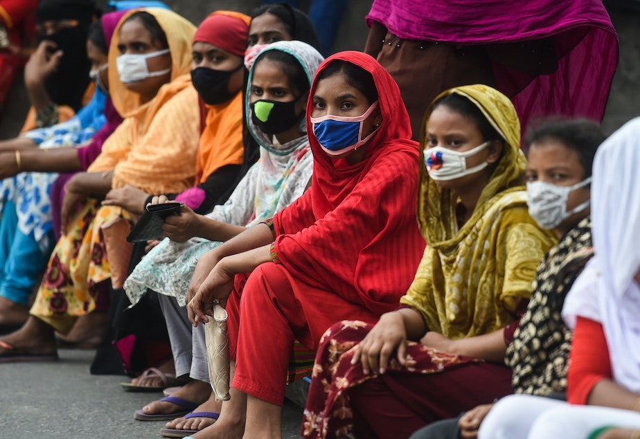 caption: Workers from the garment sector block a road during a protest to demand payment of due wages, in Dhaka, Bangladesh, in April 2020. They claimed that factories had not paid them after retailers and brands cancelled orders due to worldwide lockdown measures.