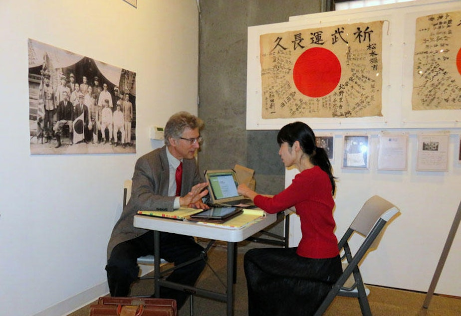 caption: Obon Society co-founders Rex and Keiko Ziak working remotely during a temporary exhibit of yosegaki hinomaru flags in Portland in 2015.