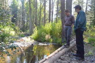 Scott Nicolai, a Yakama Nation habitat biologist, and Dave Morrow, a local landowner, observe juvenile fish in the stream they restored together.