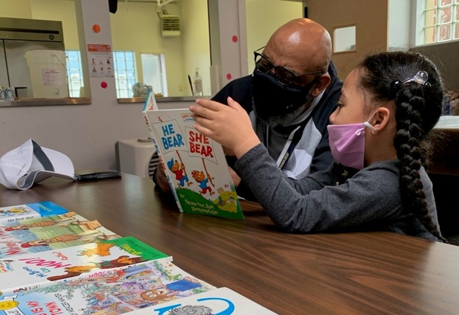 caption: Gerald  Donaldson, a family support worker at Leschi Elementary in Seattle, reads to a kindergartener at a youth center during the Covid-19 pandemic.