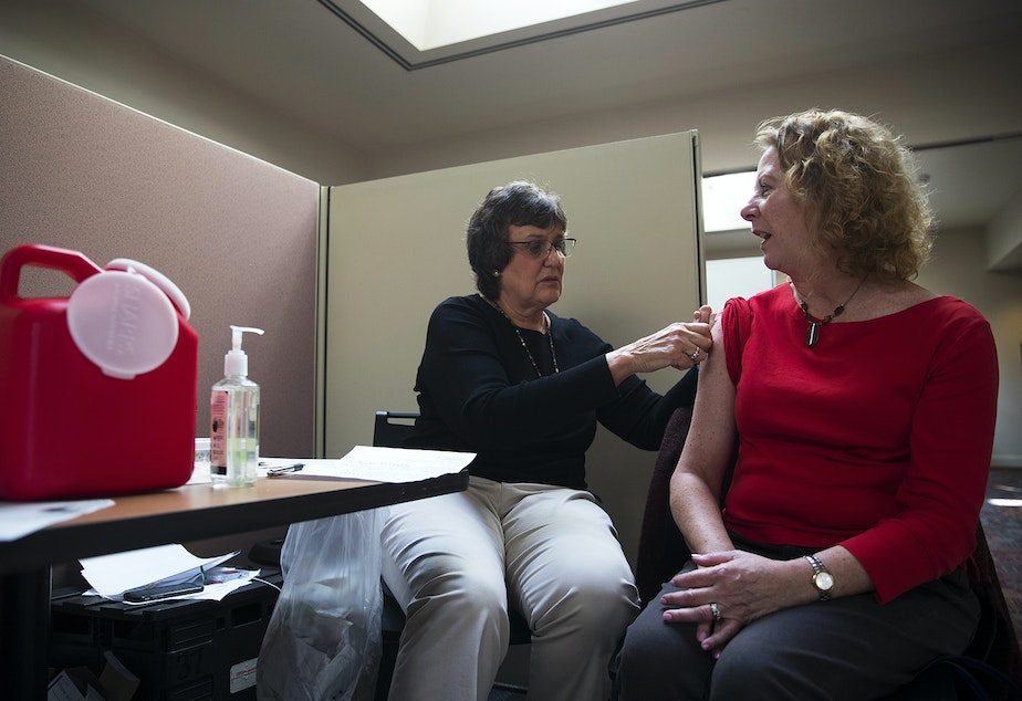 caption: Registered nurse Jeanice Smith, left, administers a flu shot for Cynthia Caci on Tuesday, October 1, 2019, at UW Tower in Seattle.