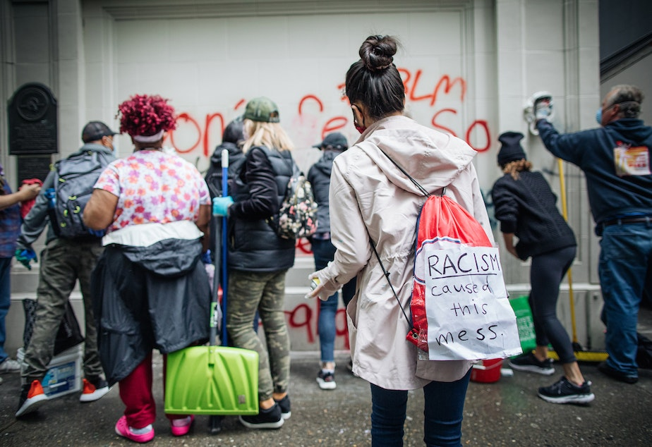 """caption: Joshua Trujillo, a Seattle photographer wrote on his Instagram page: """"Early this morning a small army descended on downtown Seattle with brooms, shovels, paint remover, gloves and masks. Instead of smelling like tear gas, on Sunday downtown Seattle smelled like paint remover and cleaning chemicals. It was a powerful scene to witness."""""""