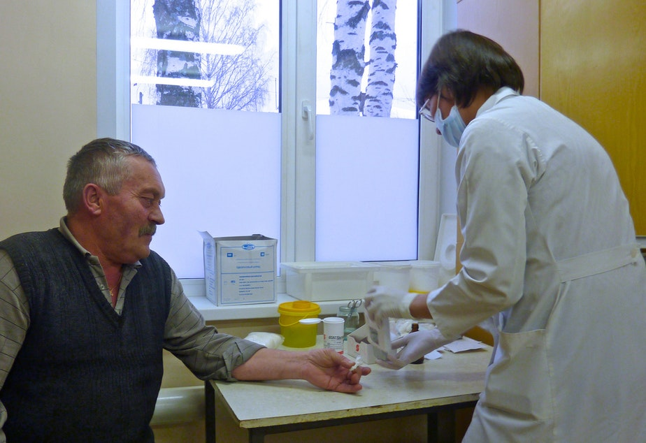 caption: A doctor takes a blood sample from an older patient.
