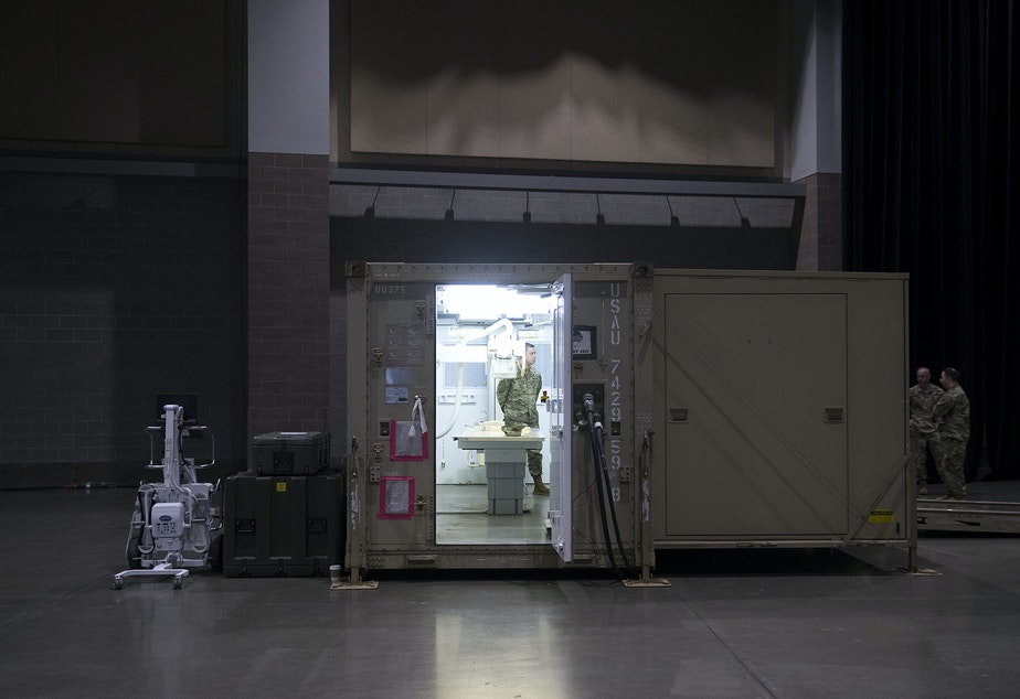 caption: U.S. Army soldiers stand in the x-ray area of the military field hospital being deployed by soldiers from the 627th Army Hospital from Fort Carson, Colorado, as well as from Joint Base Lewis-McChord on Tuesday, March 31, 2020, at the CenturyLink Field Event Center in Seattle.