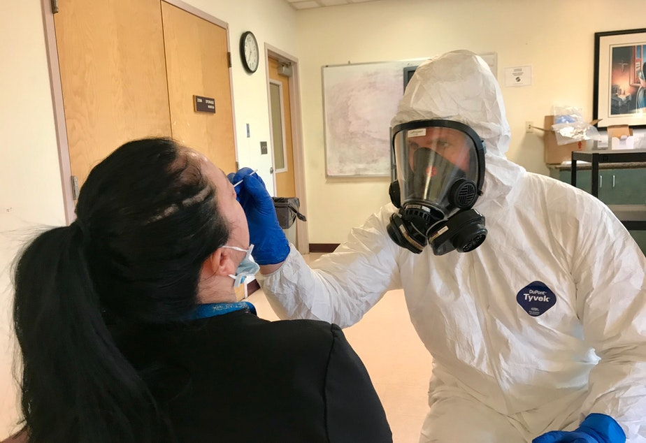 caption: SFD Paramedic Jon Leffingwell tests a staff member at a Seattle nursing home for the coronavirus.