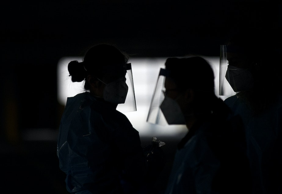 caption: QFC and Fred Meyer pharmacists wear face shields at a free drive-thru coronavirus testing site, in partnership with the city of Seattle and the Seattle Mariners, on Wednesday, May 13, 2020, in the parking garage at T-Mobile Park in Seattle.
