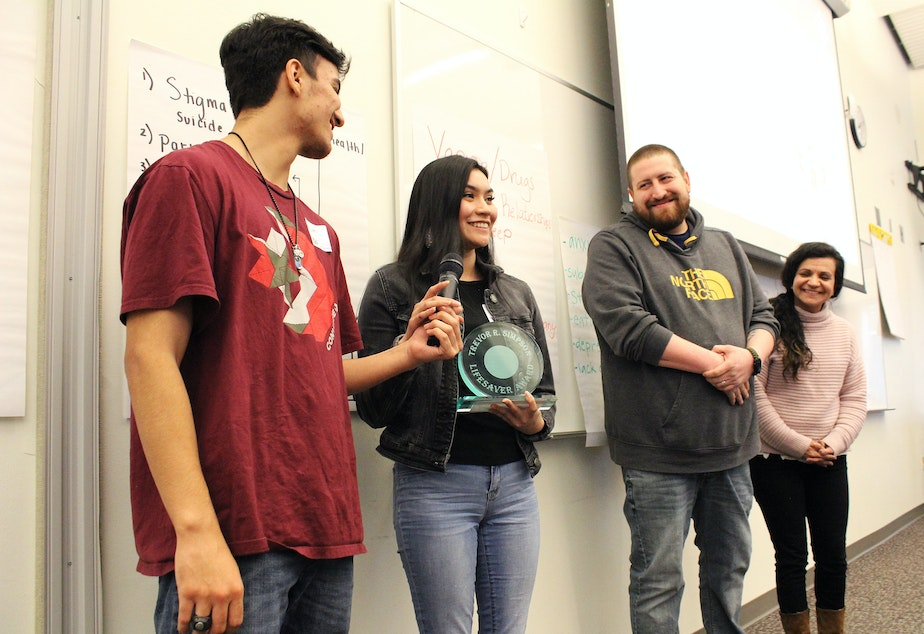 caption: From left: Seniors Dominic Jansen and Raven Stevenson, accompanied by advisers Andrew Burdette and Crissie Petro, accept the Trevor R. Simpson Award for their work as peer mentors at the Muckleshoot Tribal School.