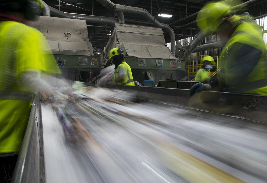 Employees remove items that cannot be recycled from a conveyer belt on Friday, October 26, 2018, at Cascade Recycling Center in Woodinville.