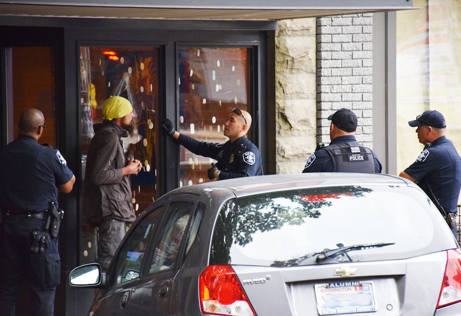 caption: Seattle Police Officer Louis Chan, center, talks with a man in Ballard about his erratic and threatening behavior. Chan is partnered with a social worker to help deescalate volatile situations.