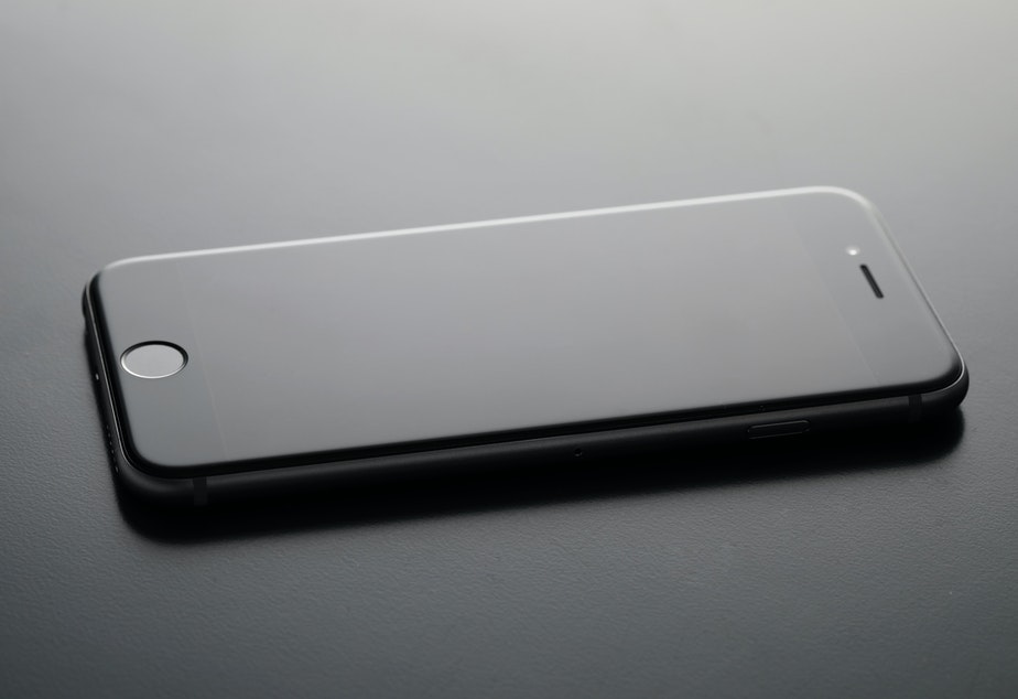 A black iphone sits on a black table top