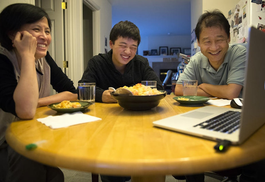 caption: The author (middle) with his mother, Guoping Ma (left), and his father, Siyuan Liu. Here they Skype over dinner with family in Tianjin, China.