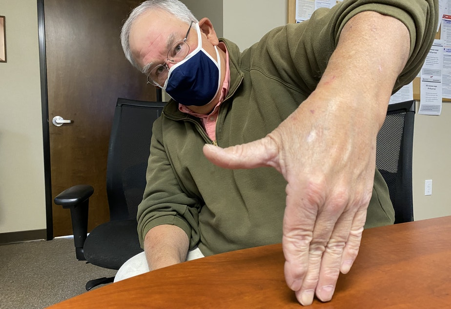 caption: Wheat rancher Chris Herron uses an old method to measure how deep his seed is being planted in his dryland furrows. Up to his thumb in soil -- that's OK. But if he sinks up to his wrist, he has to adjust the depth at which he's planting.