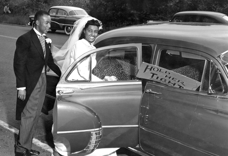 """Newlywed bride and groom stepping into car, circa 1955.  Sign in front passenger side window reads """"Hold Her Tight."""""""