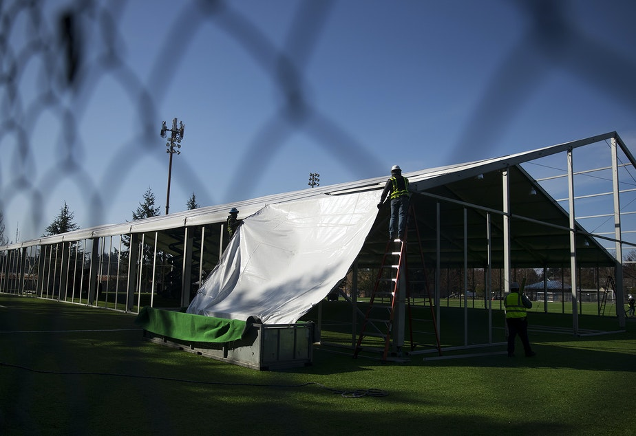 caption: A temporary 200 bed field hospital is constructed on Thursday, March 19, 2020, on a soccer field in Shoreline.